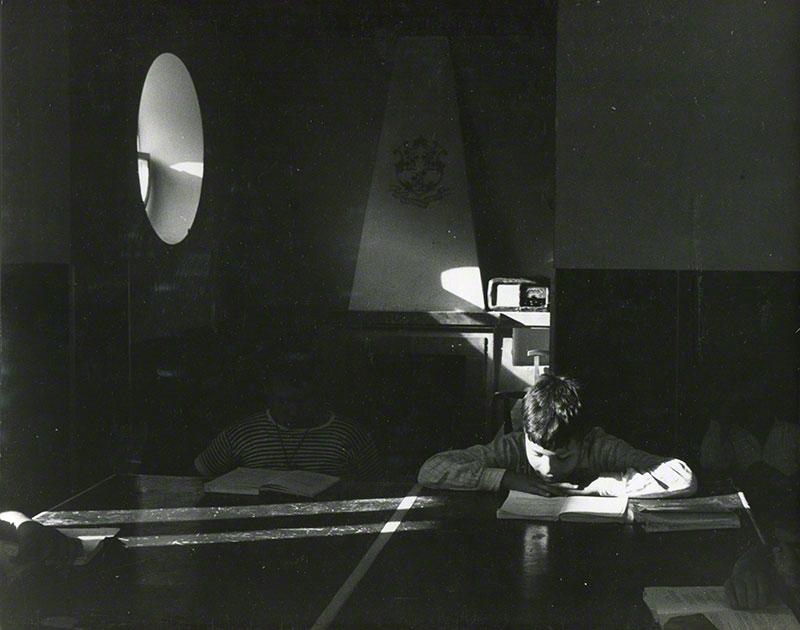 Classroom with sunlight streaming through portal window illuminating one student reading a book