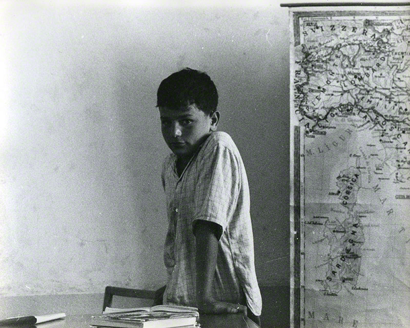 Young boy standing next to a map of Italy