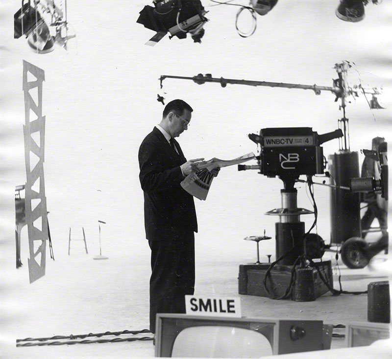 """Man in suit reading newspaper while standing in midst of cameras, lighting fixtures, microphones, and tv monitor; a """"smile"""" sign on top of monitor"""