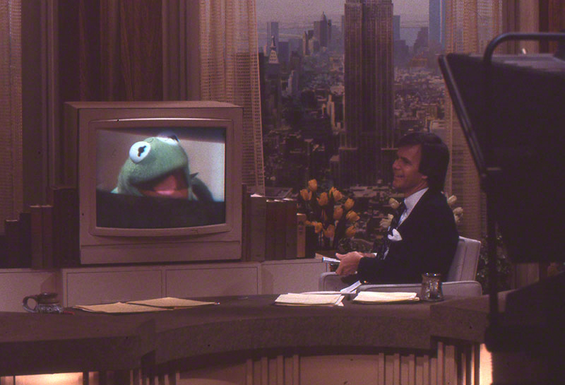 Brokaw on set, interacting with Kermit, who appears on a tv monitor