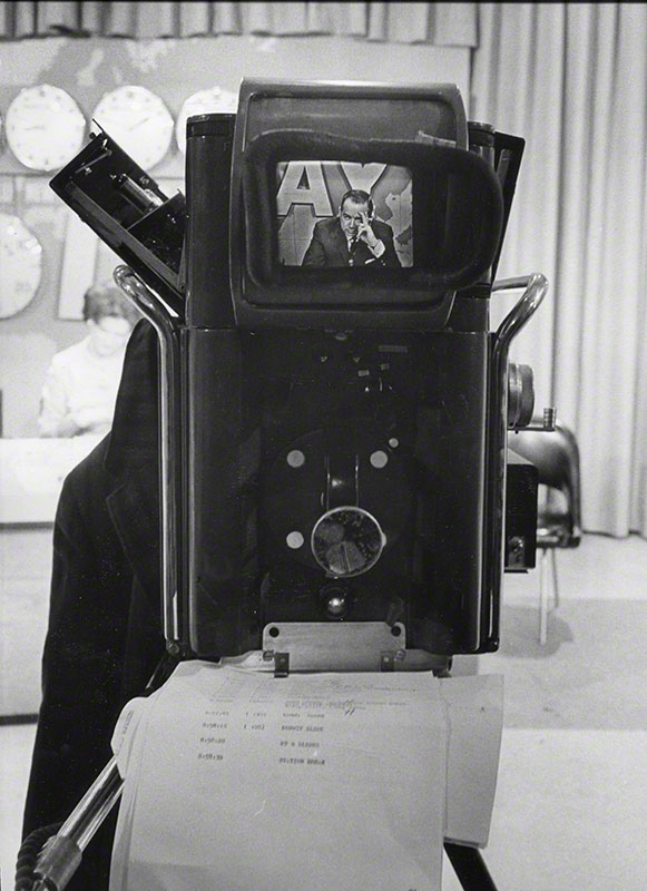 Downs seen through viewfinder of on-set equipment; in lower foreground is the image of broadcast transcripts