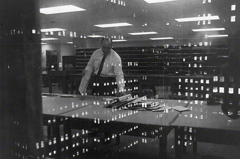 Office worker sorting through paperwork; image is overlaid with reflections of office windows from surrounding buildings