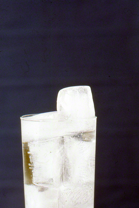 Glass of water with stacked ice cubes against royal blue background
