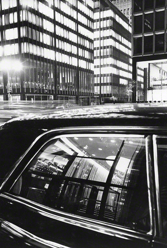 Nighttime view of lit office buildings around Park Avenue reflected in window of automobile