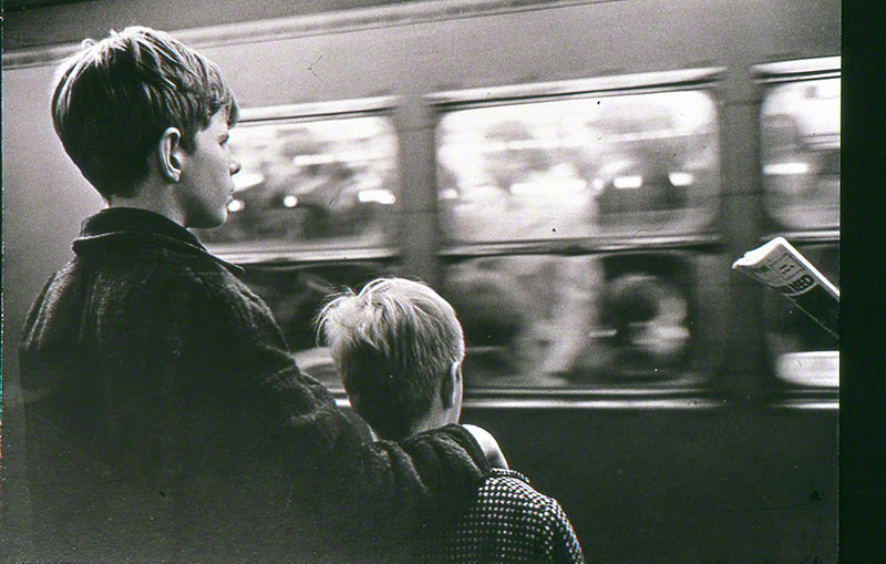 Two young boys looking at a fast moving train full of commuters