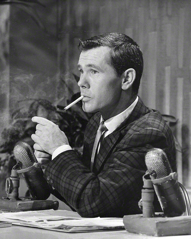 Johnny Carson sitting at his on-set desk smoking a cigarette (1962)