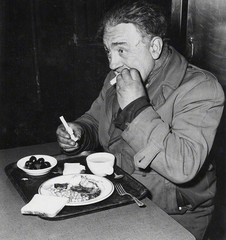 A man eating [in soup kitchen]