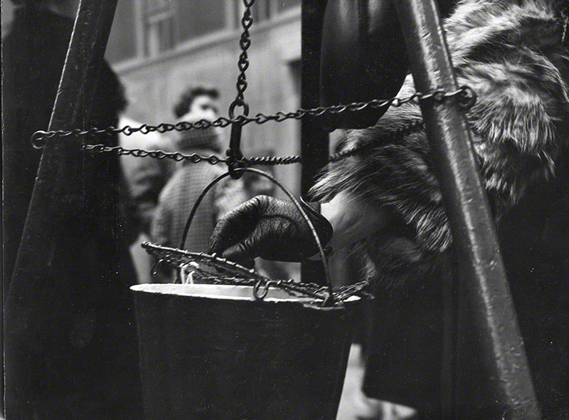 A leather gloved hand of a woman in a fur coat depositing a contribution in the Salvation Army bucket