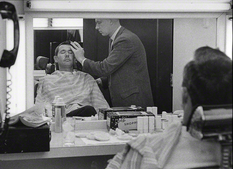 Carson having makeup applied by unidentified staffer