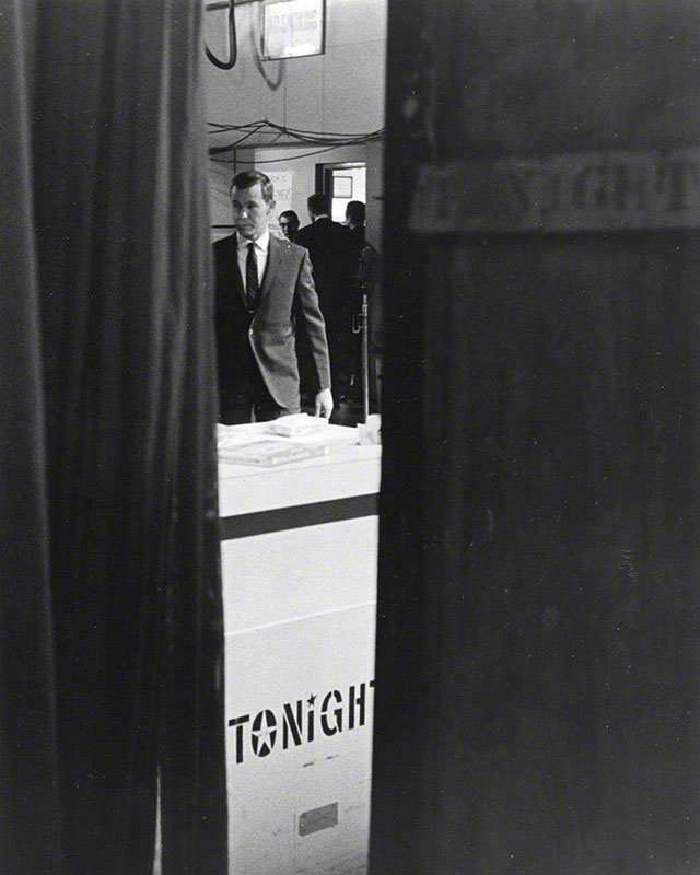 "Long shot of Carson as seen through parted curtains; counter-like structure in foreground with the word ""TONIGHT"" stenciled on."