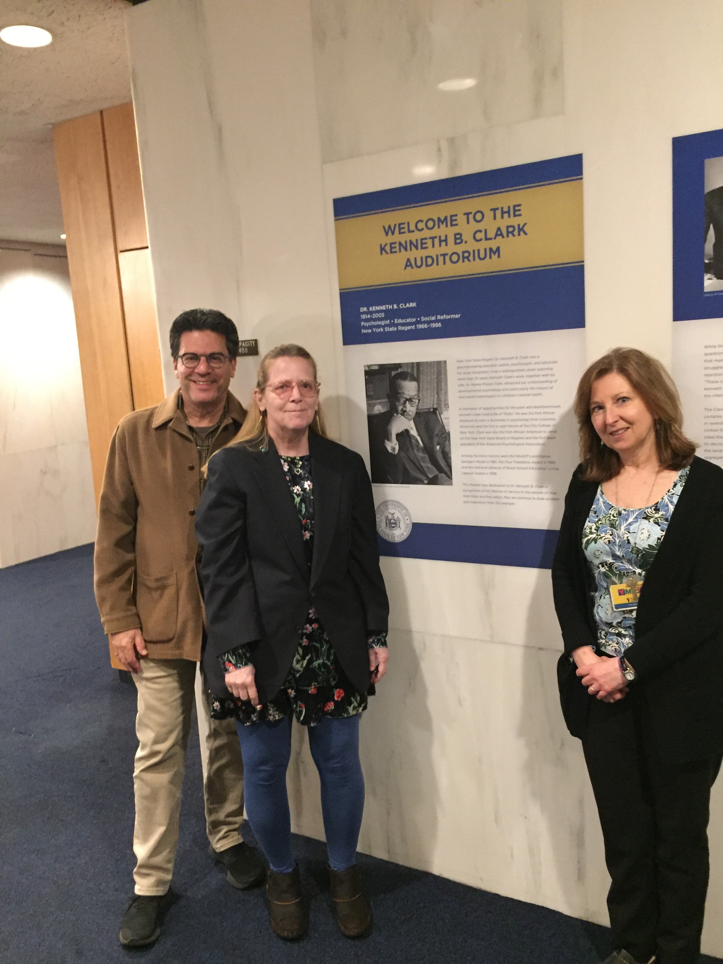 GME Fine Arts Curator David Deitch, with Carla Borea (daughter of and heir to the Estate of photographer Raimondo Borea) and Nancy Kelley, New York State Museum Director of Museum Support Services in front of wall text including Raimondo Borea's photograph of Kenneth B. Clark.