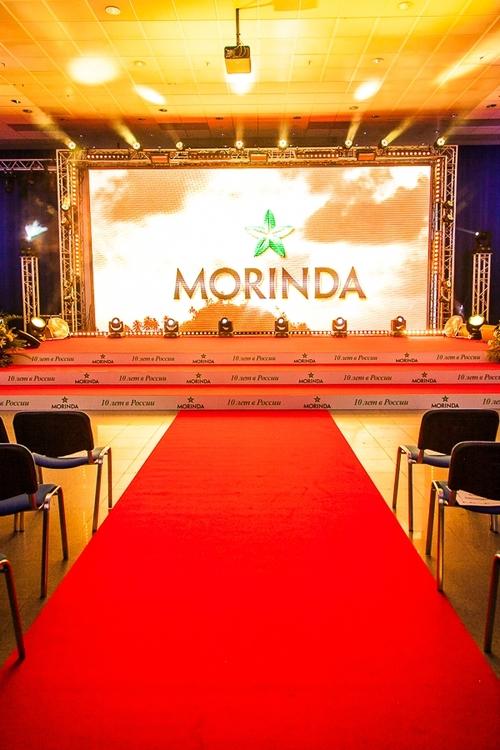 Сцена для международной компании Morinda.  Брендинг торцов ступеней, красная ковровая дорожка, большой бронированный задник сцены подчеркивают статус мероприятия на любом проекте.