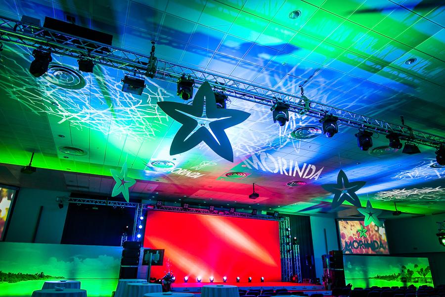 Декорации и оформление зала.  Мы всегда плотно работаем с технической службой, благодаря чему получаются такие красивые решения - световые логотипы, проецирующие на стены, отлично сочетаются с деталями, вырезанными из пластика, а светодиодный экран с баночными стенами.
