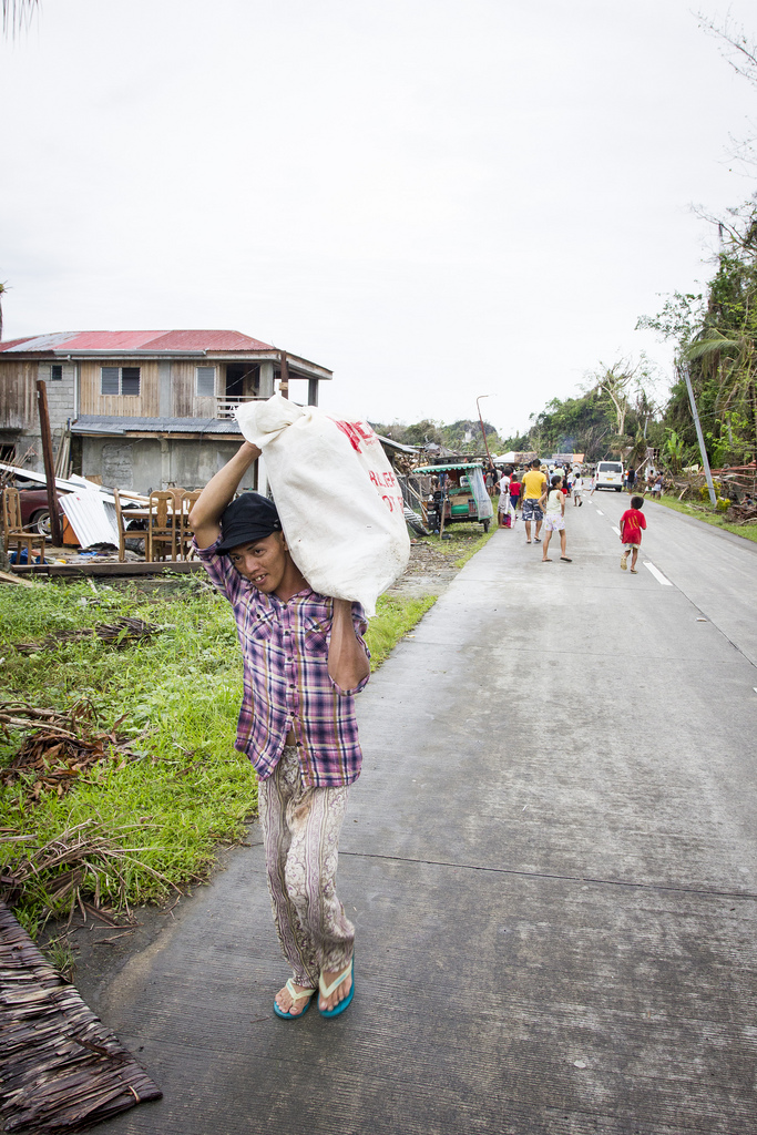 A man carries a bag of rice, distributed by the Filipino army in the wake of Typhoon Haiyan, back to his house in Veloso, Samar.