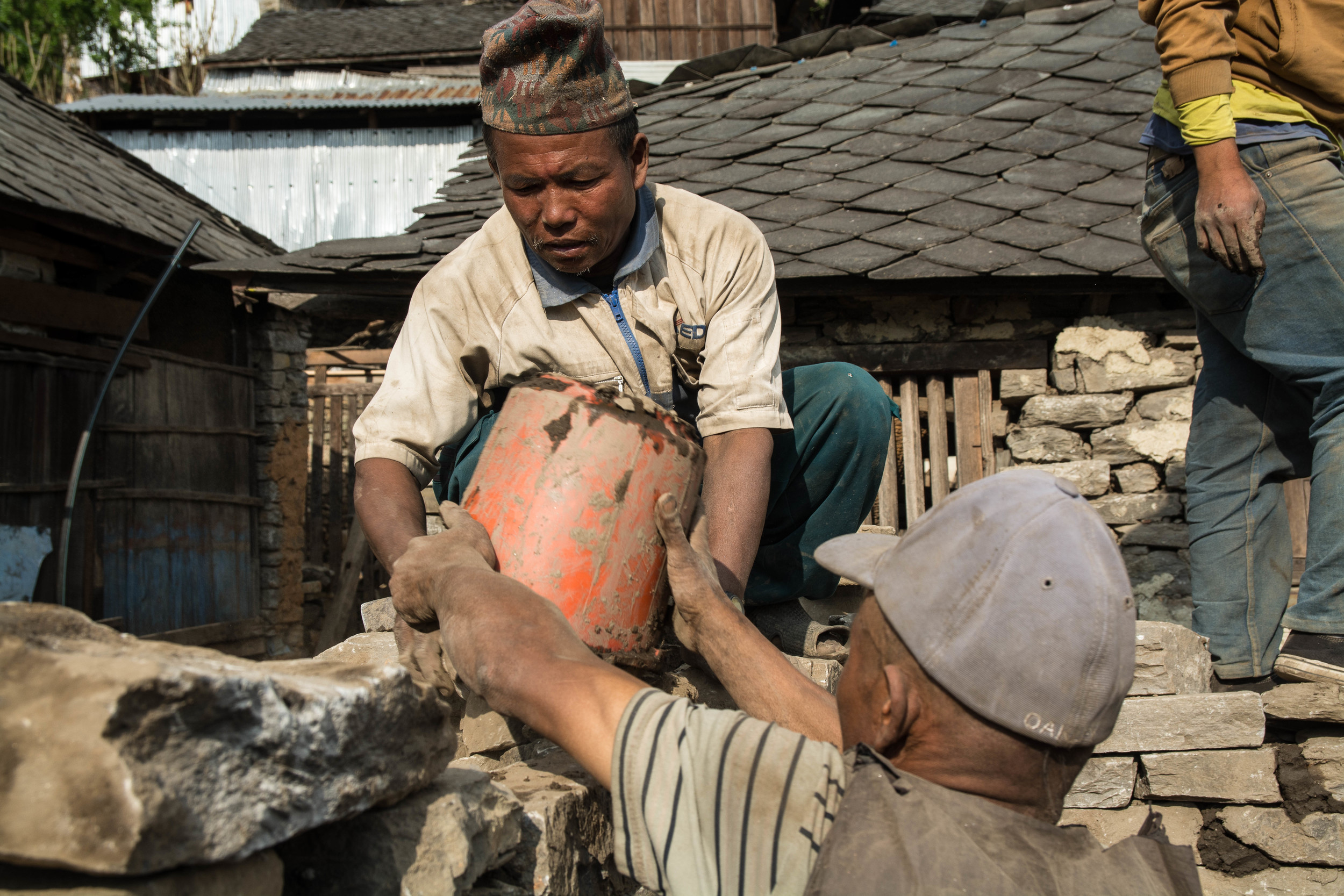 Shree Bahadur Tamang's neighbors apply mud to one of the stone walls of his house - photo by Mark Morrison.