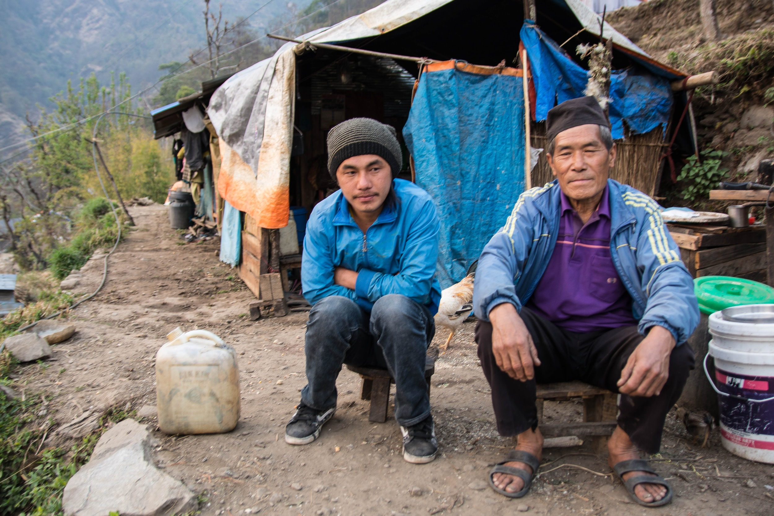 Pream Bahadur Tamang, right, and his family are still living under their tarpaulin-covered shelter. He has been watching his neighbors rebuild their houses and has decided to wait and see if their homes last through the upcoming monsoon season before he decides whether or not to rebuild his own house. His family, including his son Bir, left, disagree with his decision - Photo by Mark Morrison.