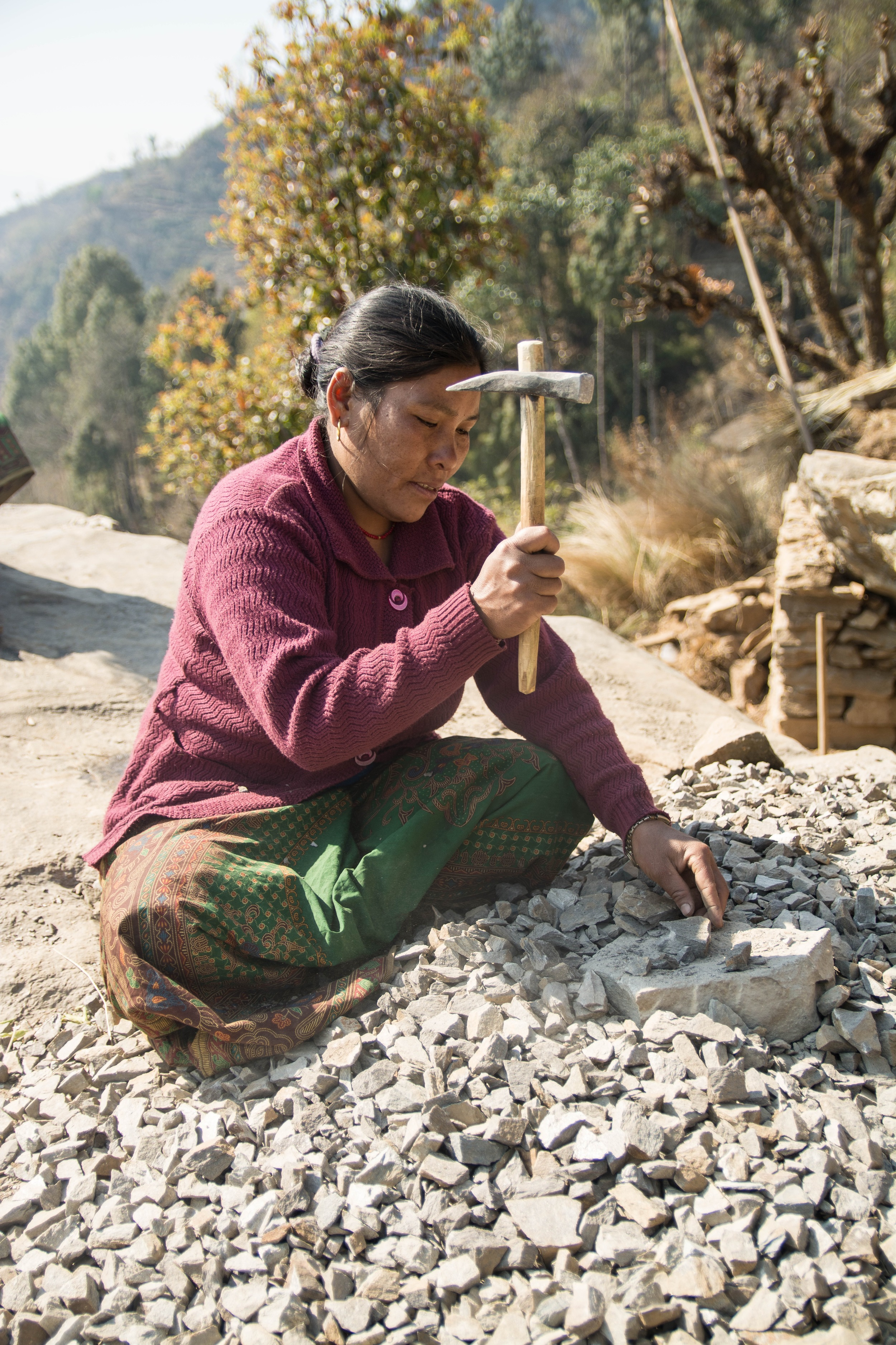 Kalimaya Tamang breaks stone that will be used to rebuild the church building in Ewe - Photo by Mark Morrison.