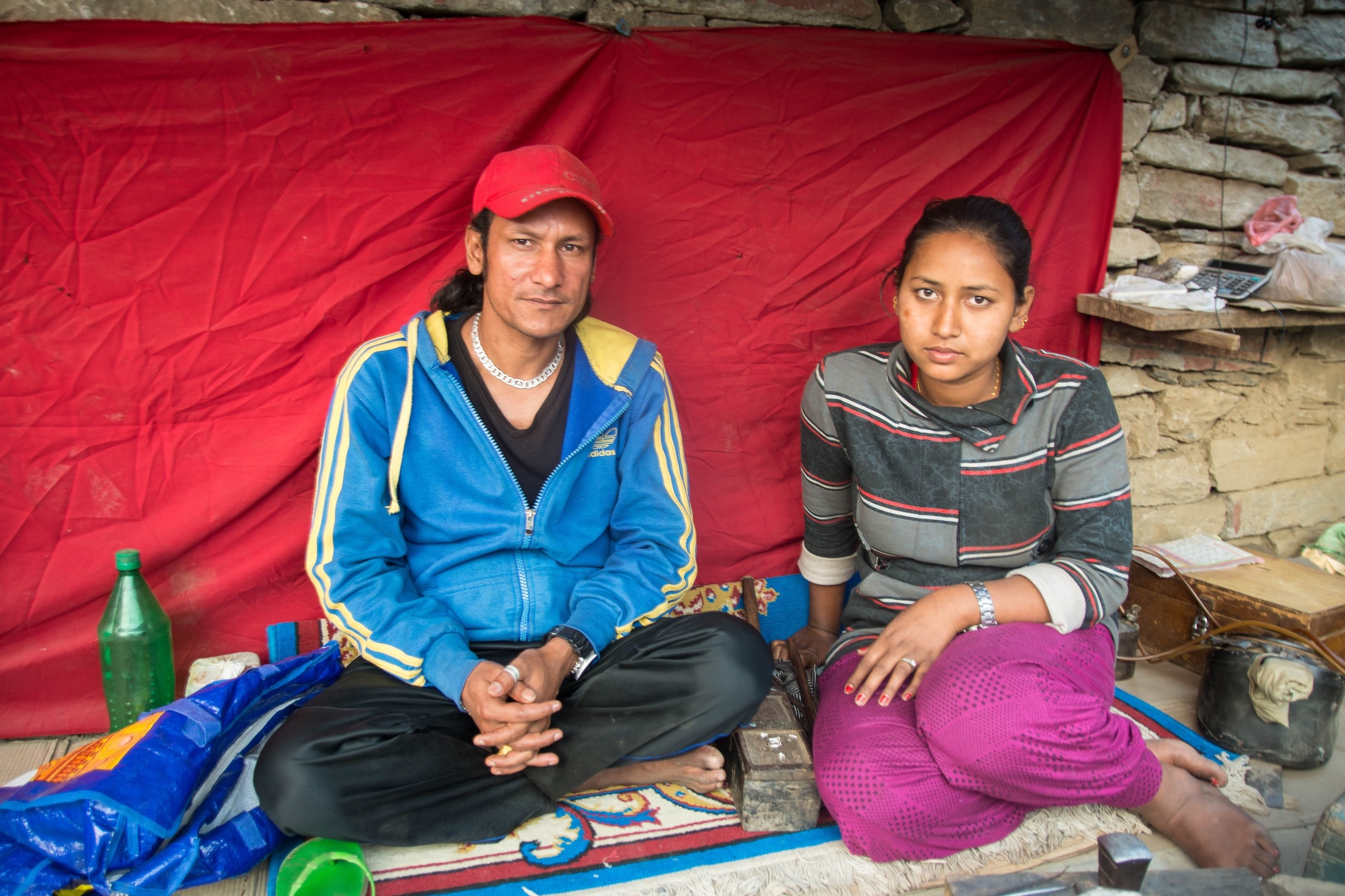 "Ram Kumar, left, and Bhawana Sunar, right, are jewelry makers in Tawal. Kumar was trapped by falling rock during the earthquake. Bone in both his legs were shattered and his head was cut open and bleeding. Despite receiving treatment, he is still in great pain. ""It's not safe here,"" he said. ""I am feeling weak...it's hard to walk."" - Photo by Mark Morrison."