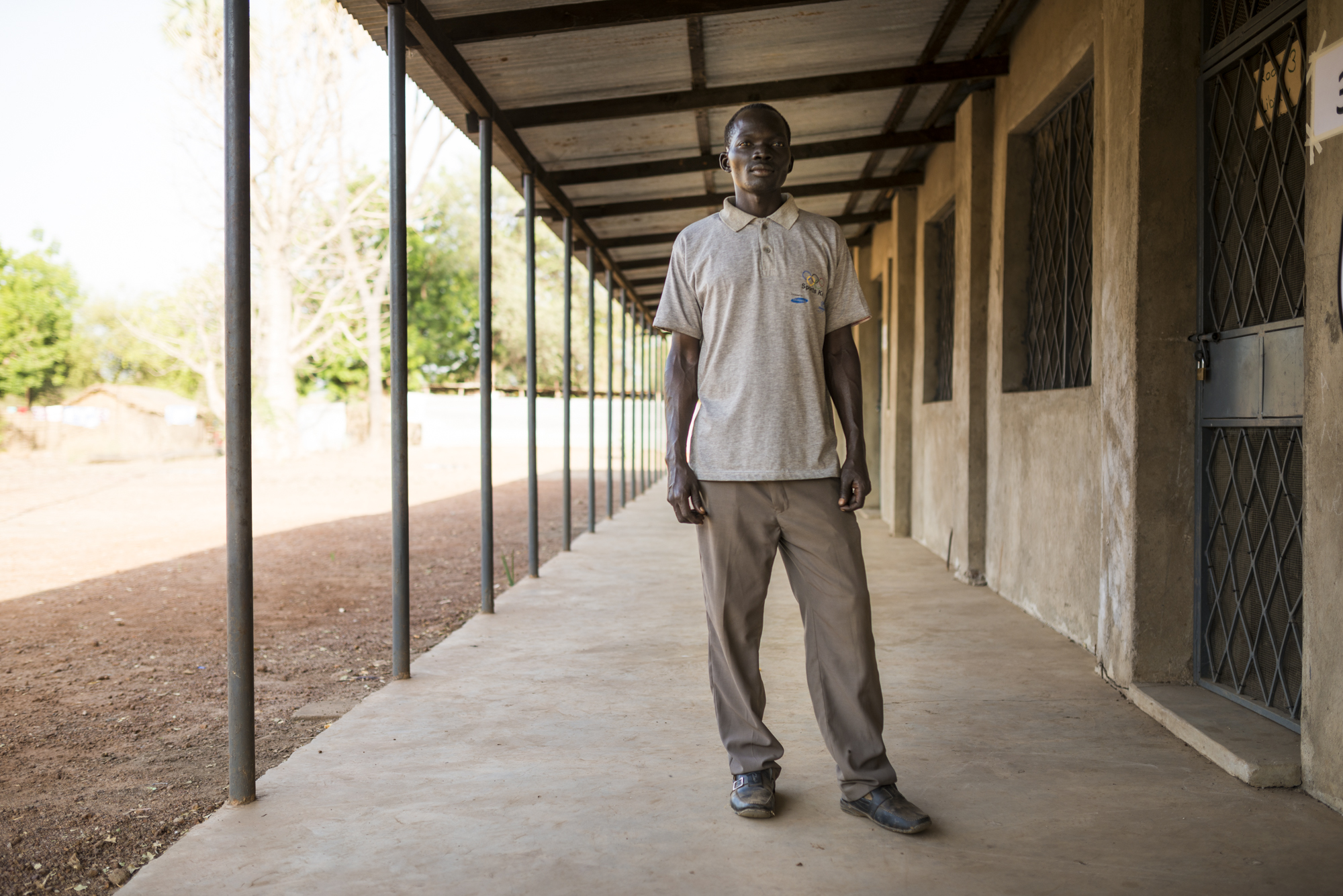 Graduate Wella Samuel stands outside the current SIC secondary school in Doro. He now works for Save the Children helping vulnerable young children in the camps. Photo credit - Tim Coleman