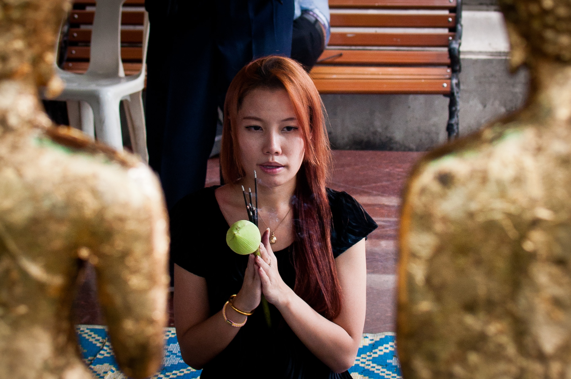 A woman prays and offers incense at Wat Pho in Bangkok. Most of Prang's family is still Buddhist and take issue with Prang becoming a Christian. Photo courtesy of  Mark Fischer .