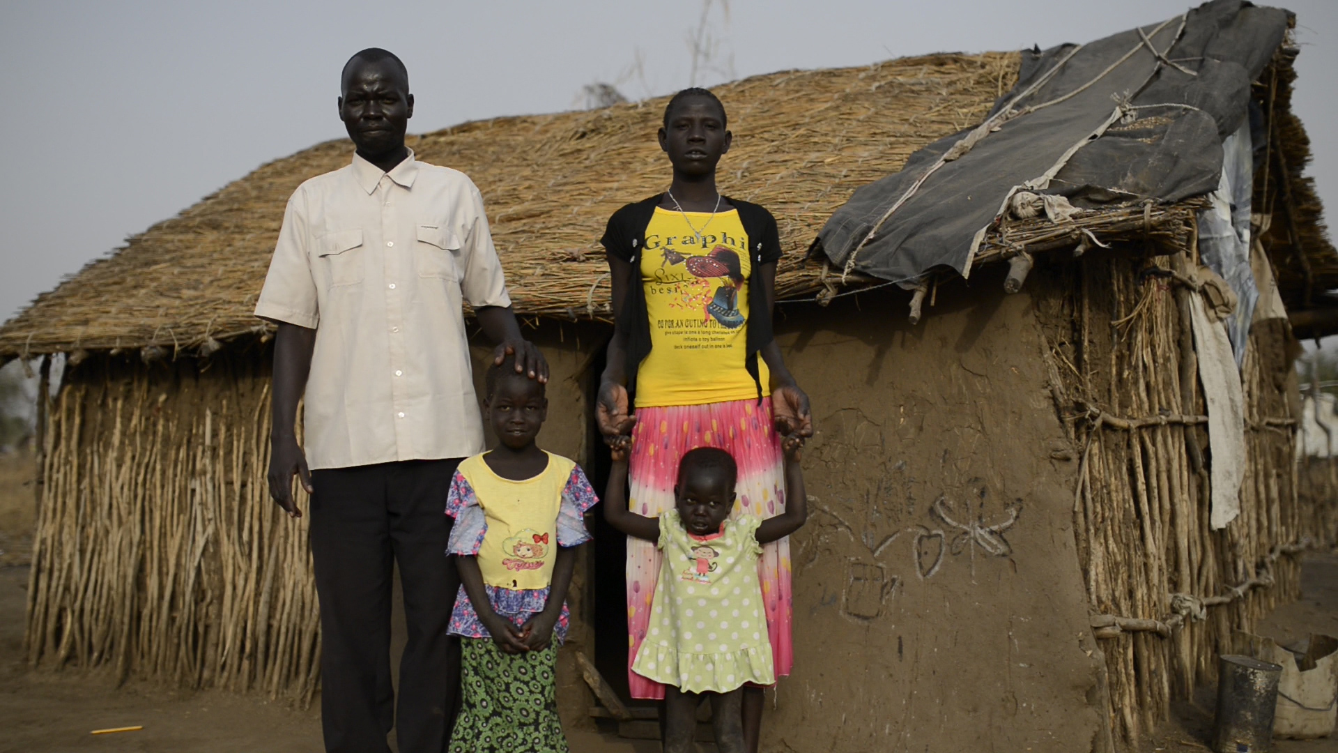 Dikem with his wife and two of his children outside their home in the refugee camp close to SIC Secondary School