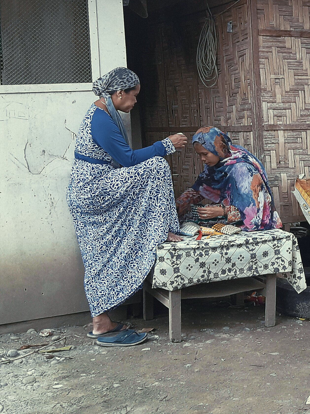 Two of the Chora women prepare finished wallets for export and sale - Photo by Desseri.