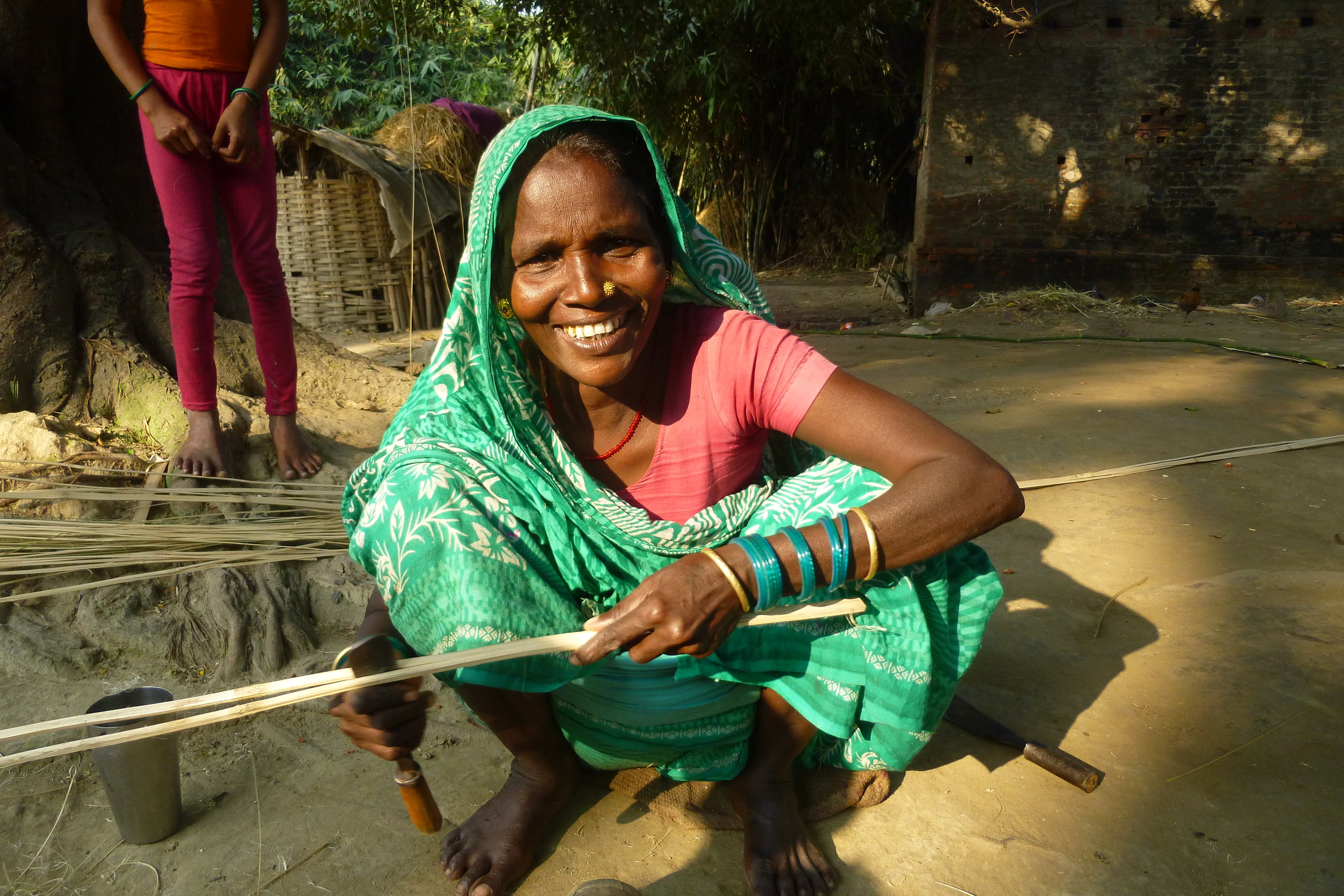 Ramseki makes bamboo into slats so they can be used to make the traditional handicrafts her caste has been making for generations - Photo by Sarah K.