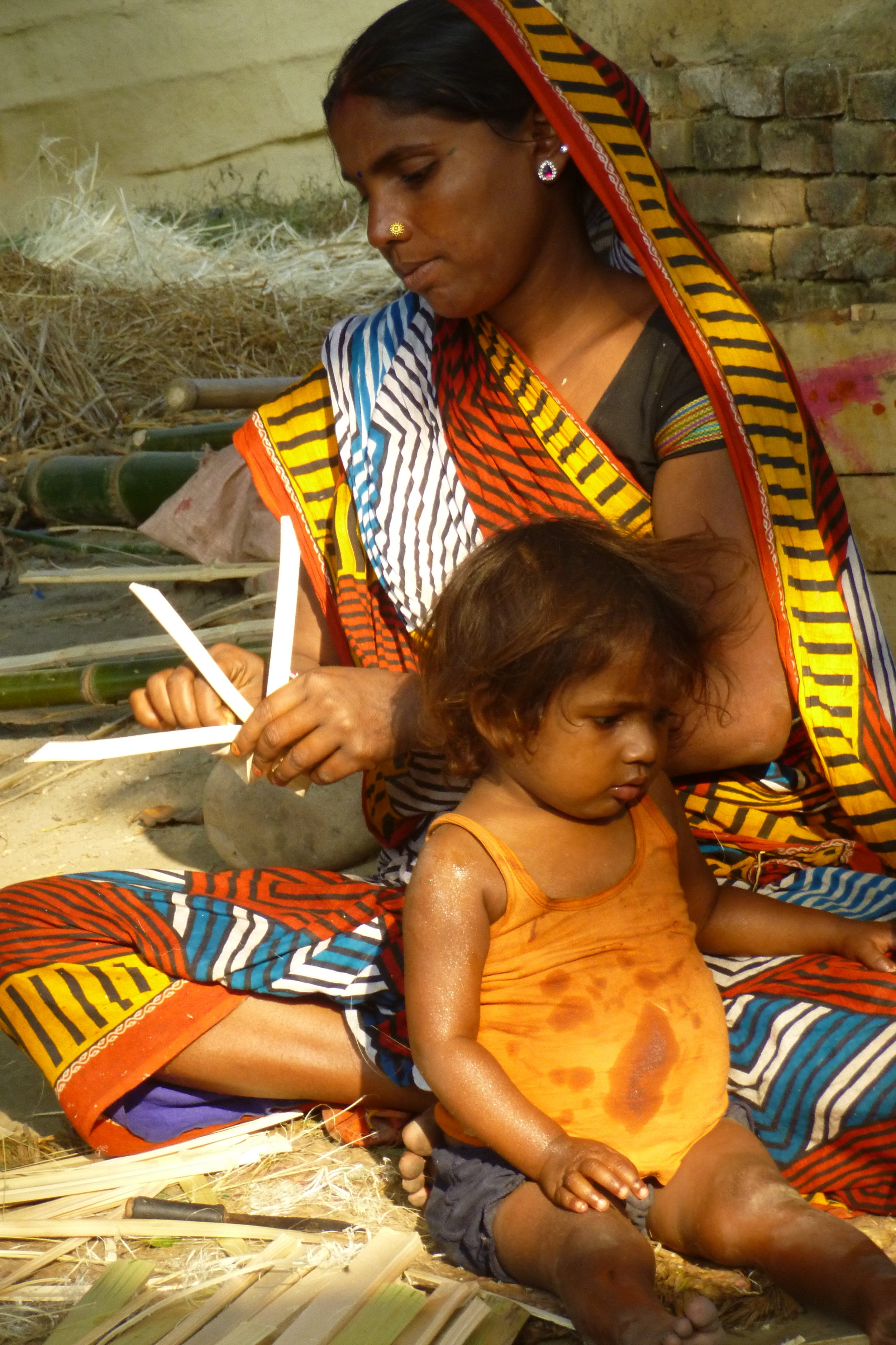 Sita begins on a design for a bamboo flower with her youngest beside her - Photo by Sarah K.