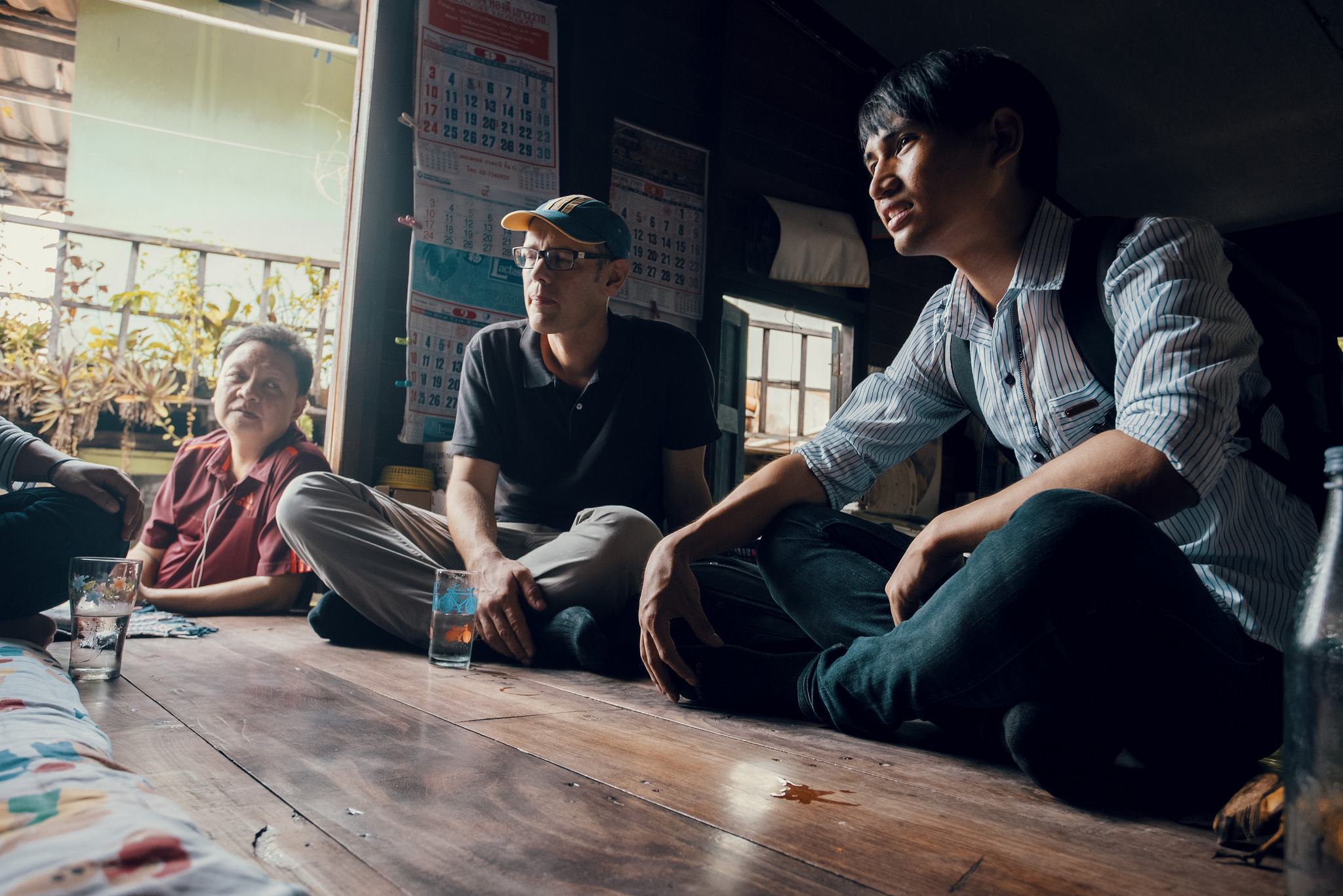 "Stefan (centre) and Thai intern, Tee (right) listen as one of the ""aunties"" in the community talks. Pii Daeng (left), the Rac Chum Chon team's Thai leader, listens from the doorway."