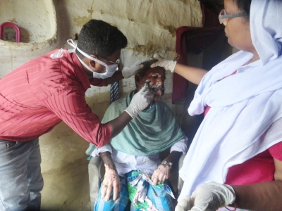 Chetna staff cleans a wound caused by mouth cancer. Photo courtesy of Natalie.