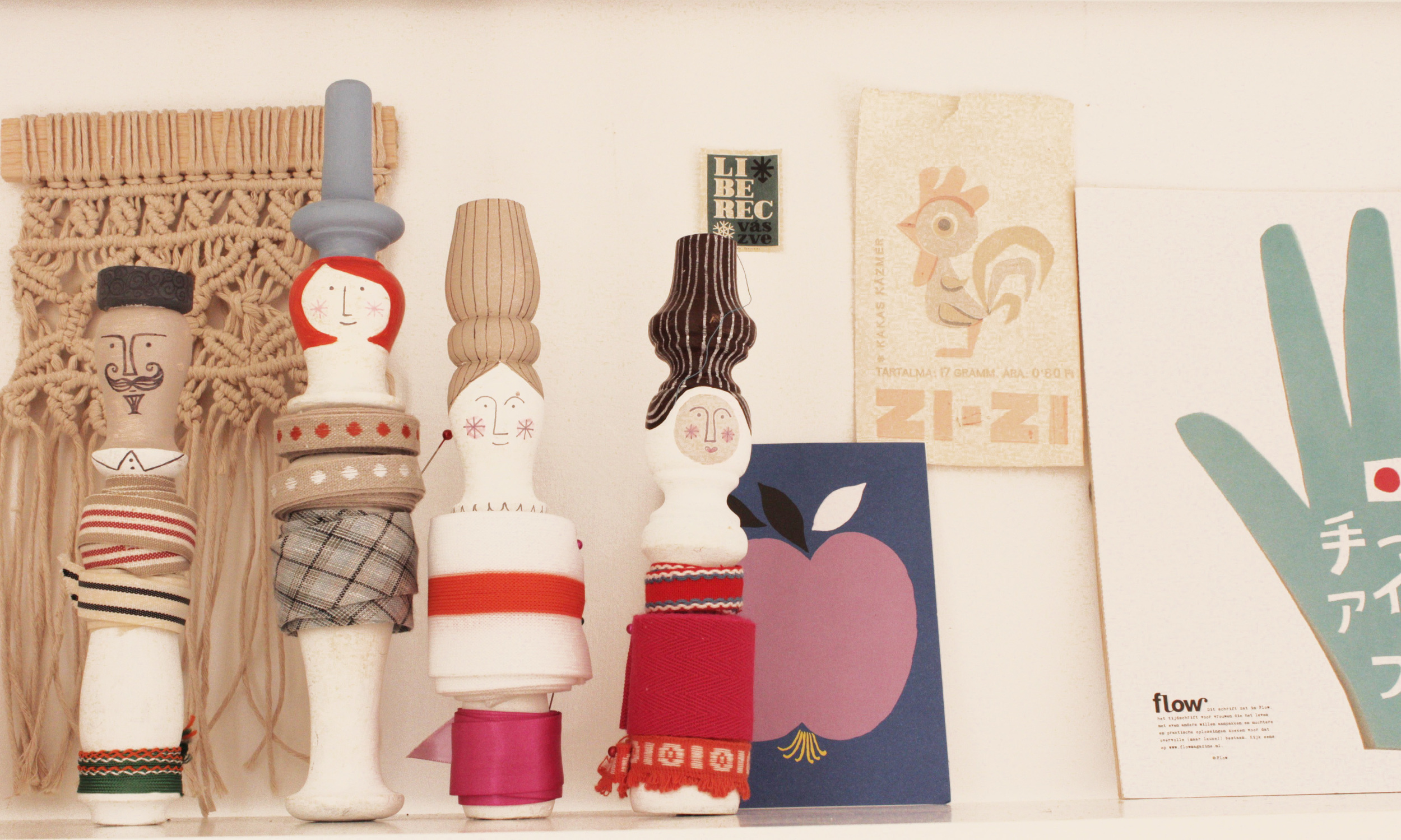 A few of Clare's makes and paper clippings that inspire her lined up on a bookcase.