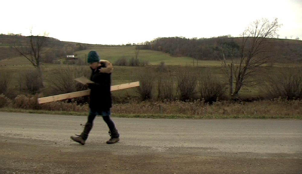 re-enacting carrying planks to the barn (first of three men)