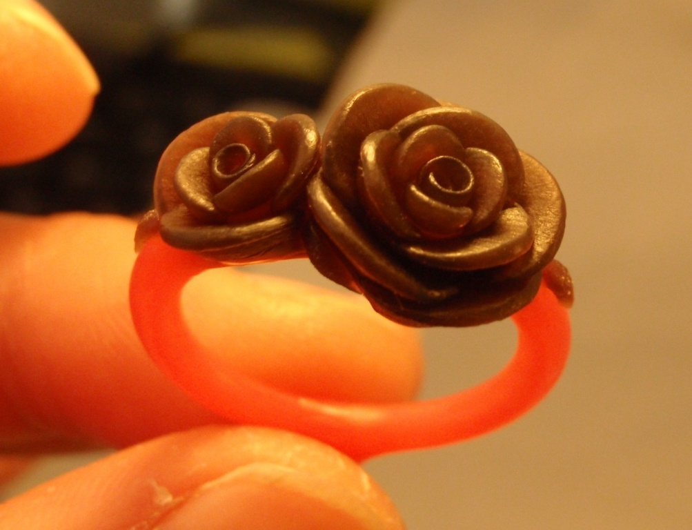 A sculpted model of a ring with two roses.
