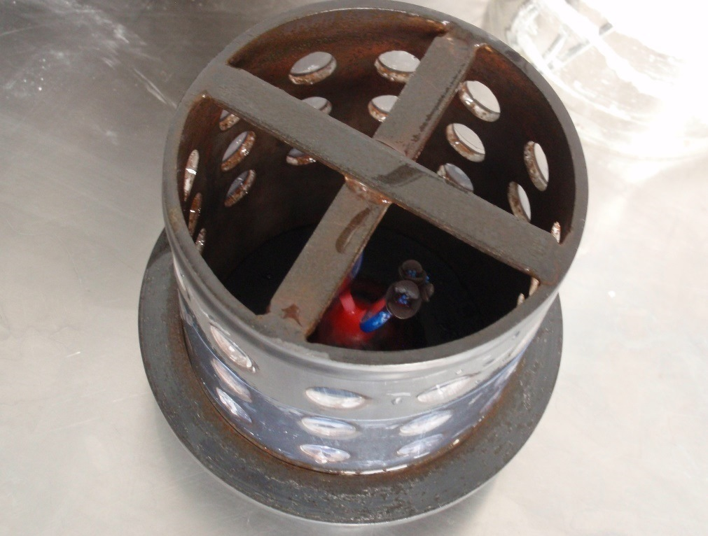 A steel flask is secured over the base, with a tree of ring models inside.