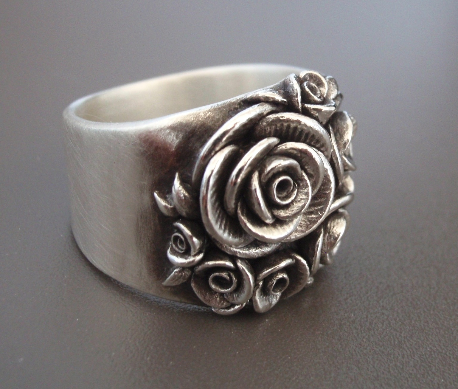 A finished Bouquet of Roses, wide-band ring.