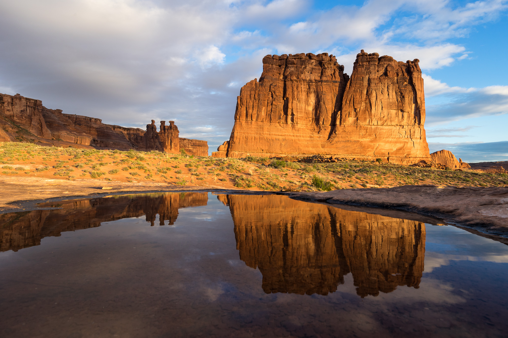 Courthouse Towers Reflecting in Pothole Below Clearing Storm, Arches National Park, Utah
