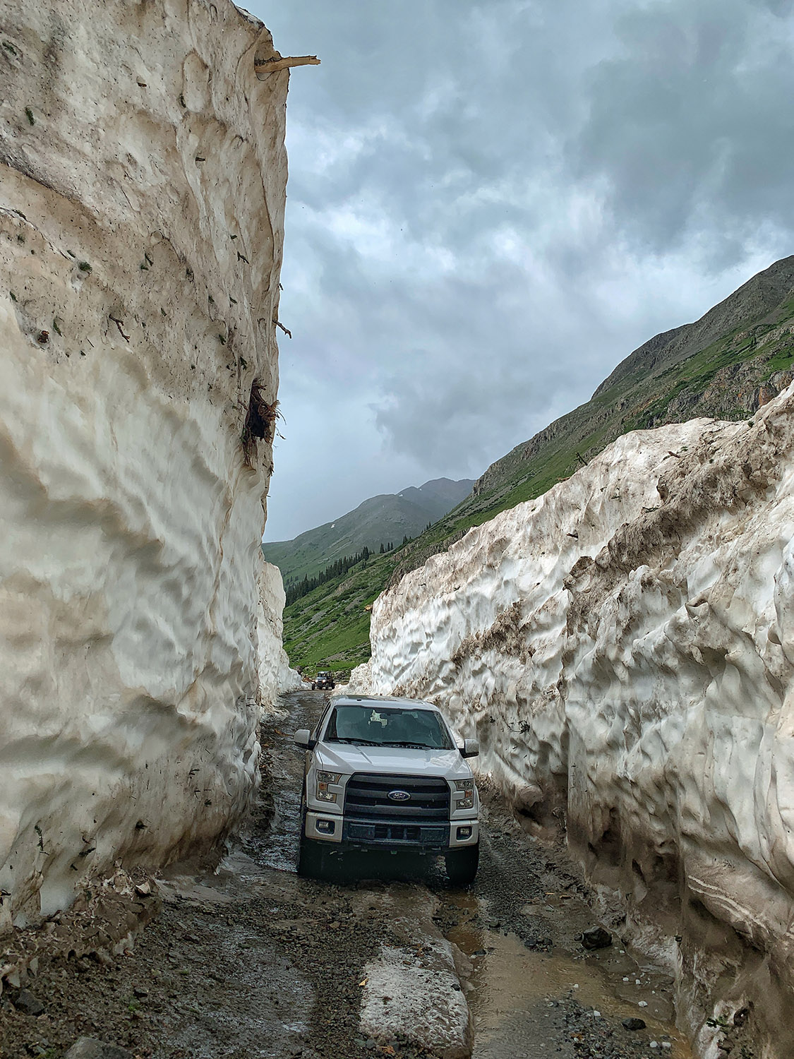 The San Juan Mountains experienced a snowy winter and Betty stopped to pose in a narrow cut through a massive avalanche debris flow en route to Animas Forks ghost town outside Silverton, Colorado.