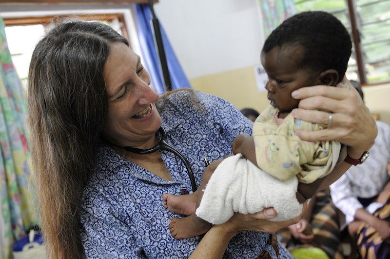 Dr. Terrie Taylor with a child in the clinic of the Blantyre Malaria Project.