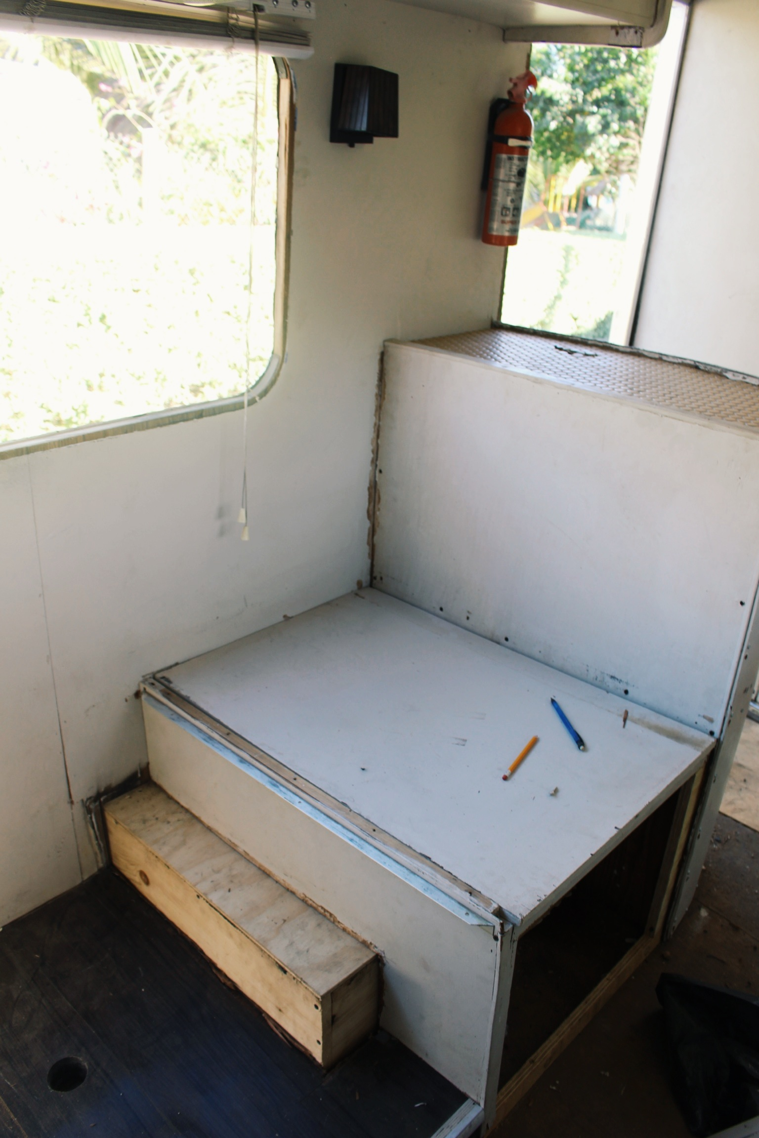 The back side of the entry cabinet, which doubles as the dining seat backrest, which sits on top of the wheel well and also serves as a cabinet. Everything multitasks in an RV.
