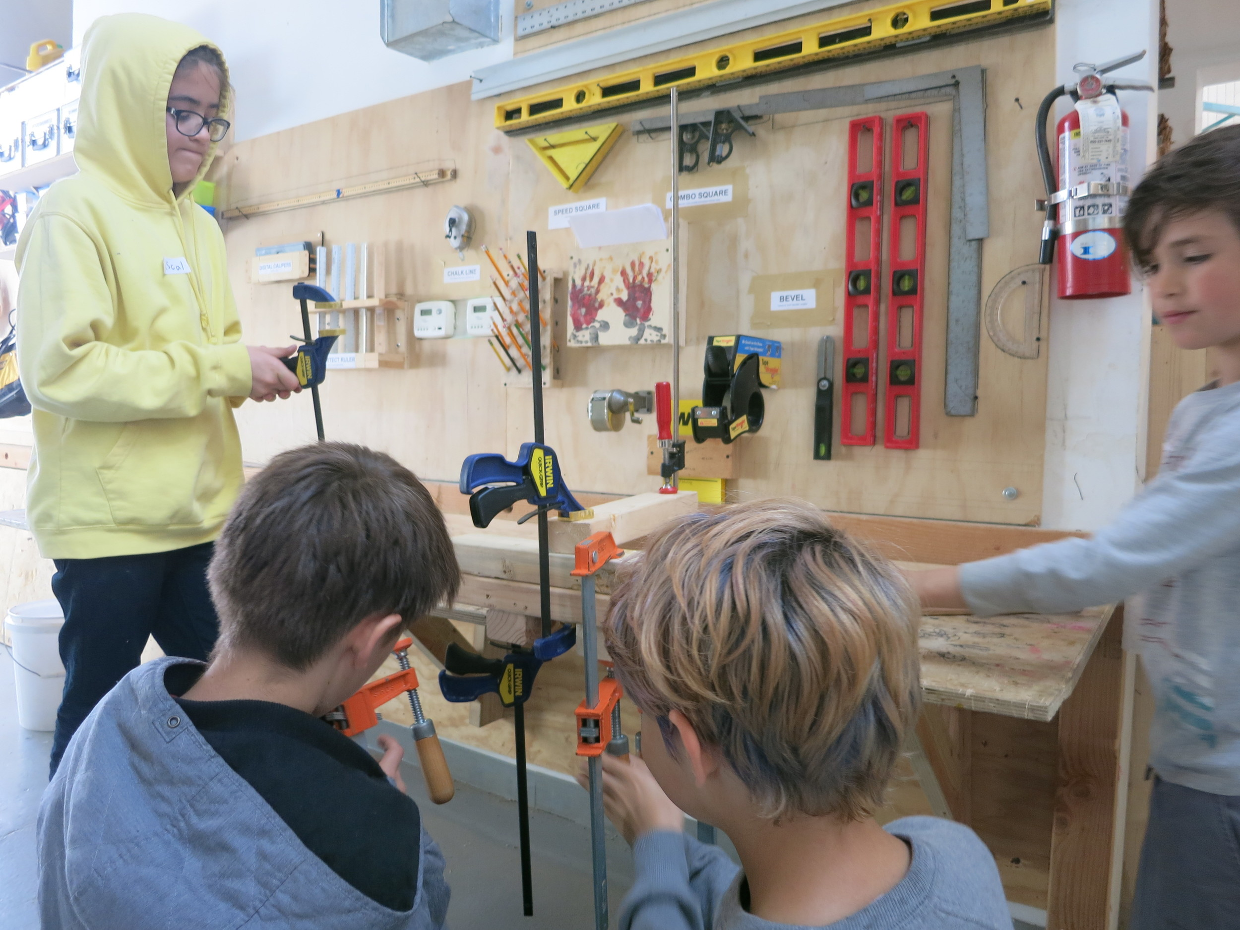 Pascal, Romy, Jacob, and Isaac work together to get the hang of clamps.