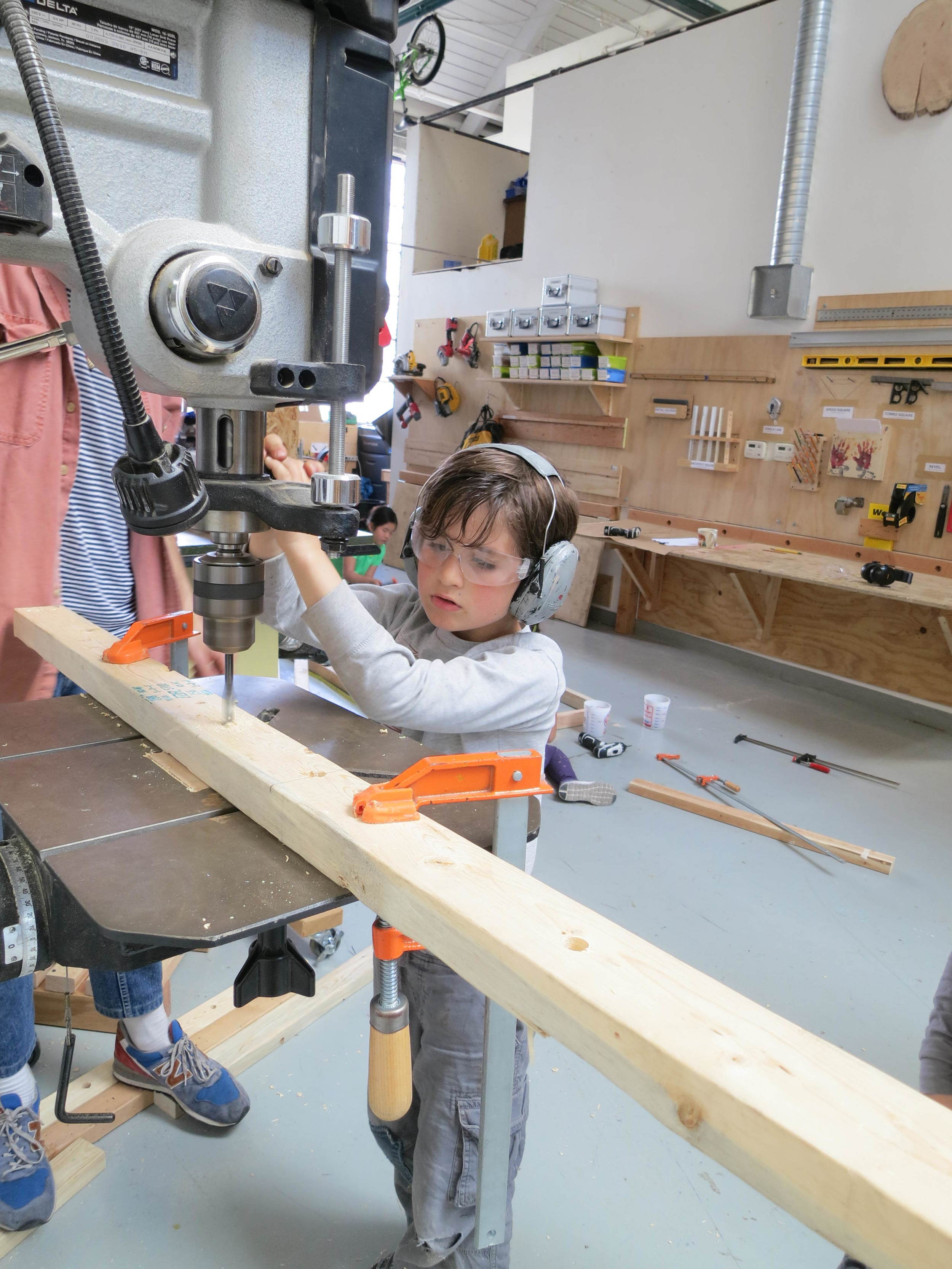 Isaac uses the drill press to make large diameter holes for the Ring Toss project.