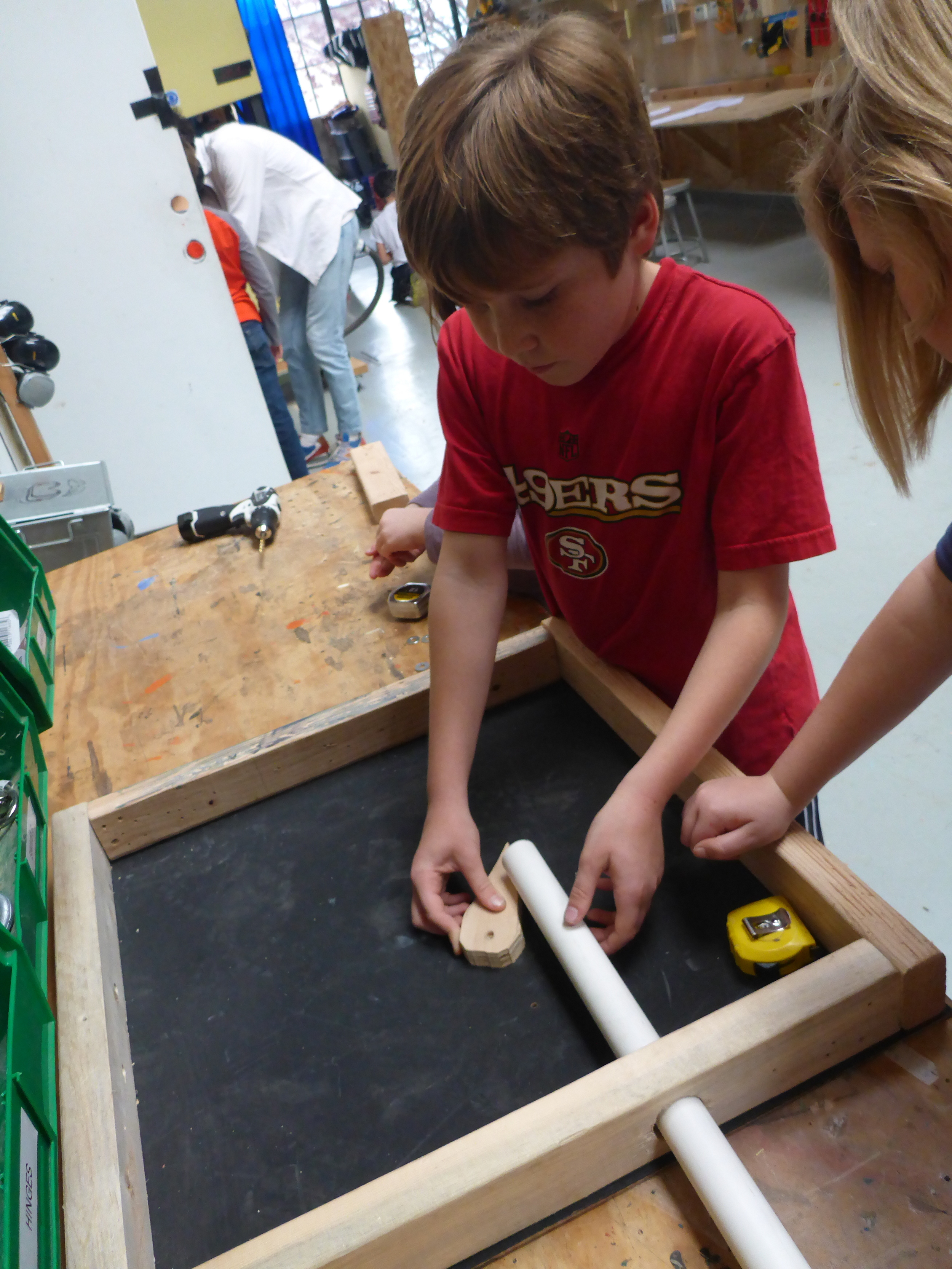 Henry and Sunny determine placement for the flipper to be controlled by pushing on a piece of PVC.
