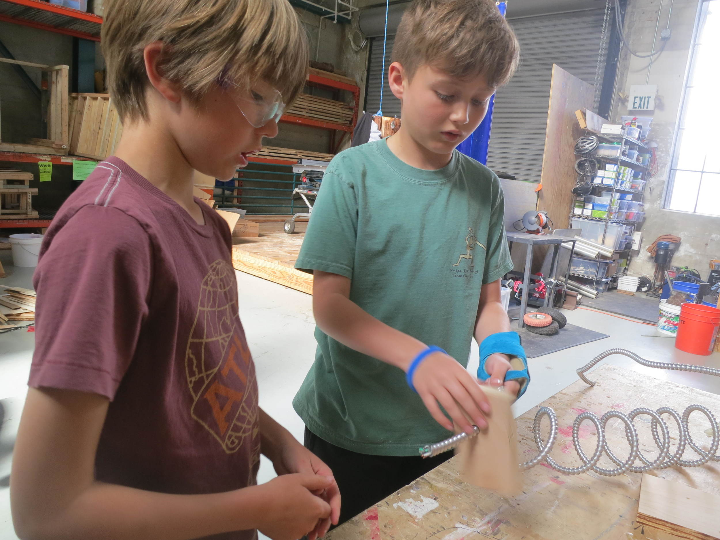 Henri and Ethan try using the end of the coil as a handle to turn the coil inside the box.
