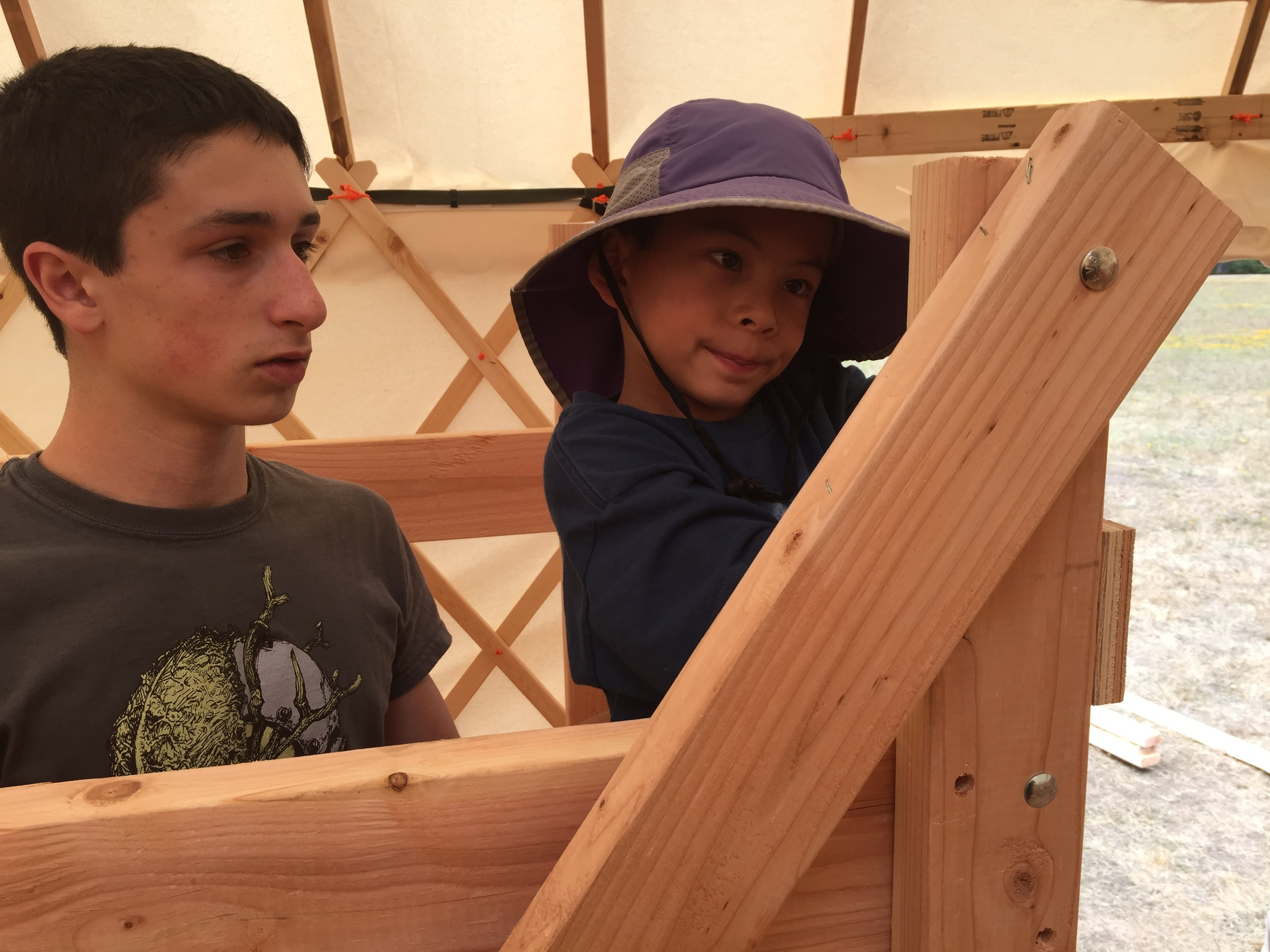 Nico works with Leo to start installing a safety bar on one of the bunks.
