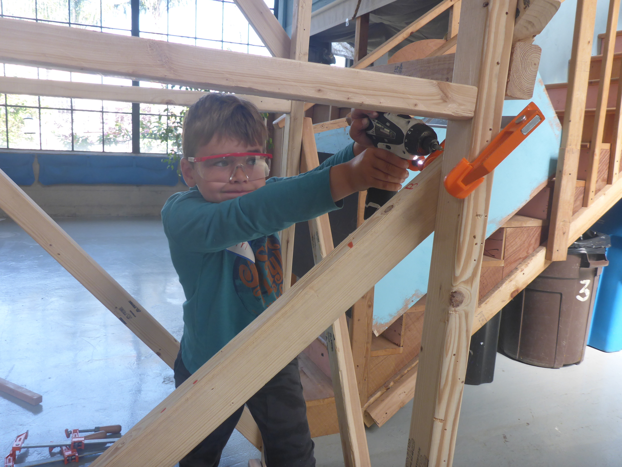 The only disadvantage to building really tall things is that it's sometimes verydifficult to drive in screws that are above shoulder level. Ari is intensely focused on completing the bridge supports, even though the work is really hard!