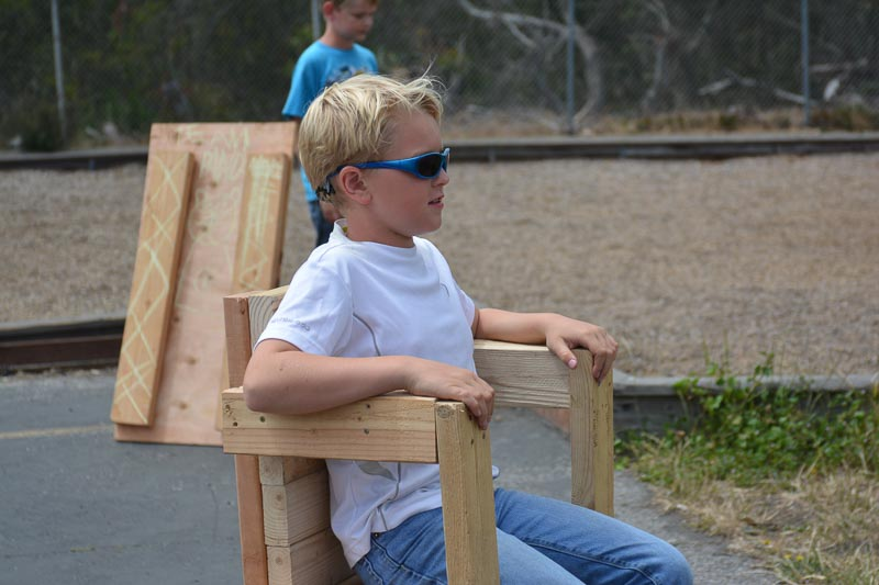 Portrait of a Tinkerer: Ryker sits in a chair of his own making