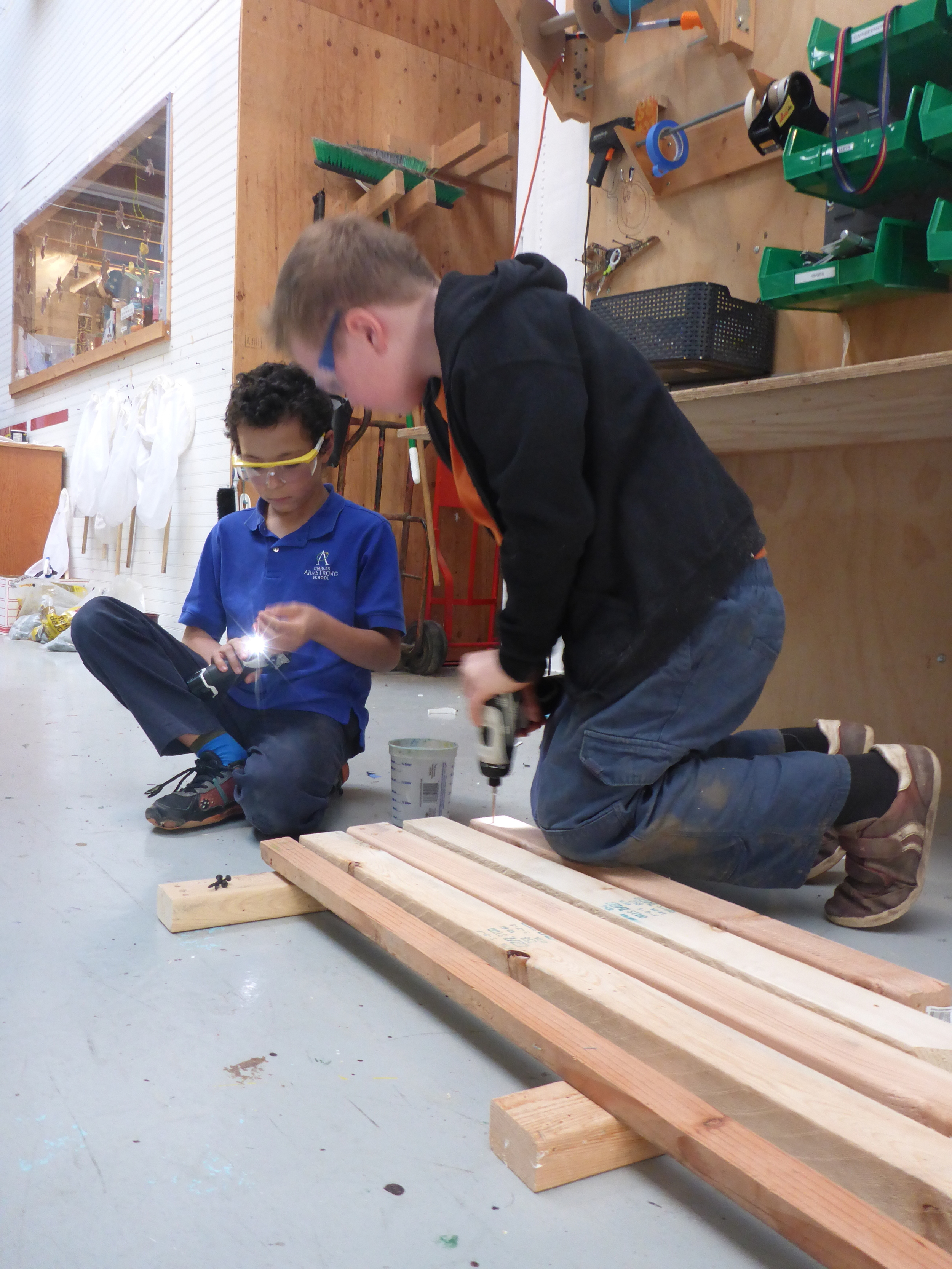 Assembling the first draft (prototype) of a giant wooden xylophone. Tinkerers experimented with clanking wooden boards of different lengths and found that the shorter boards made higher sounds! They were also pretty excited to use the power drills.