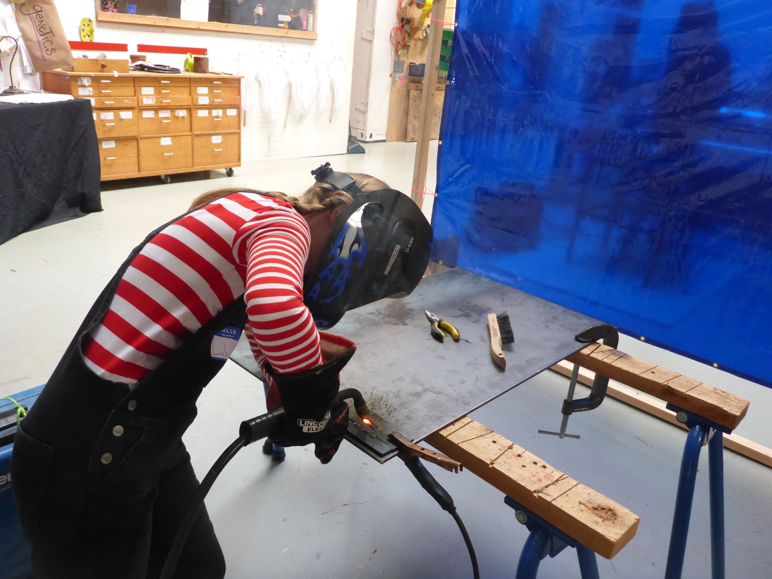 Lulu carefully stabilizes her body with one elbow resting on the welding table so that she can make a longer weld.