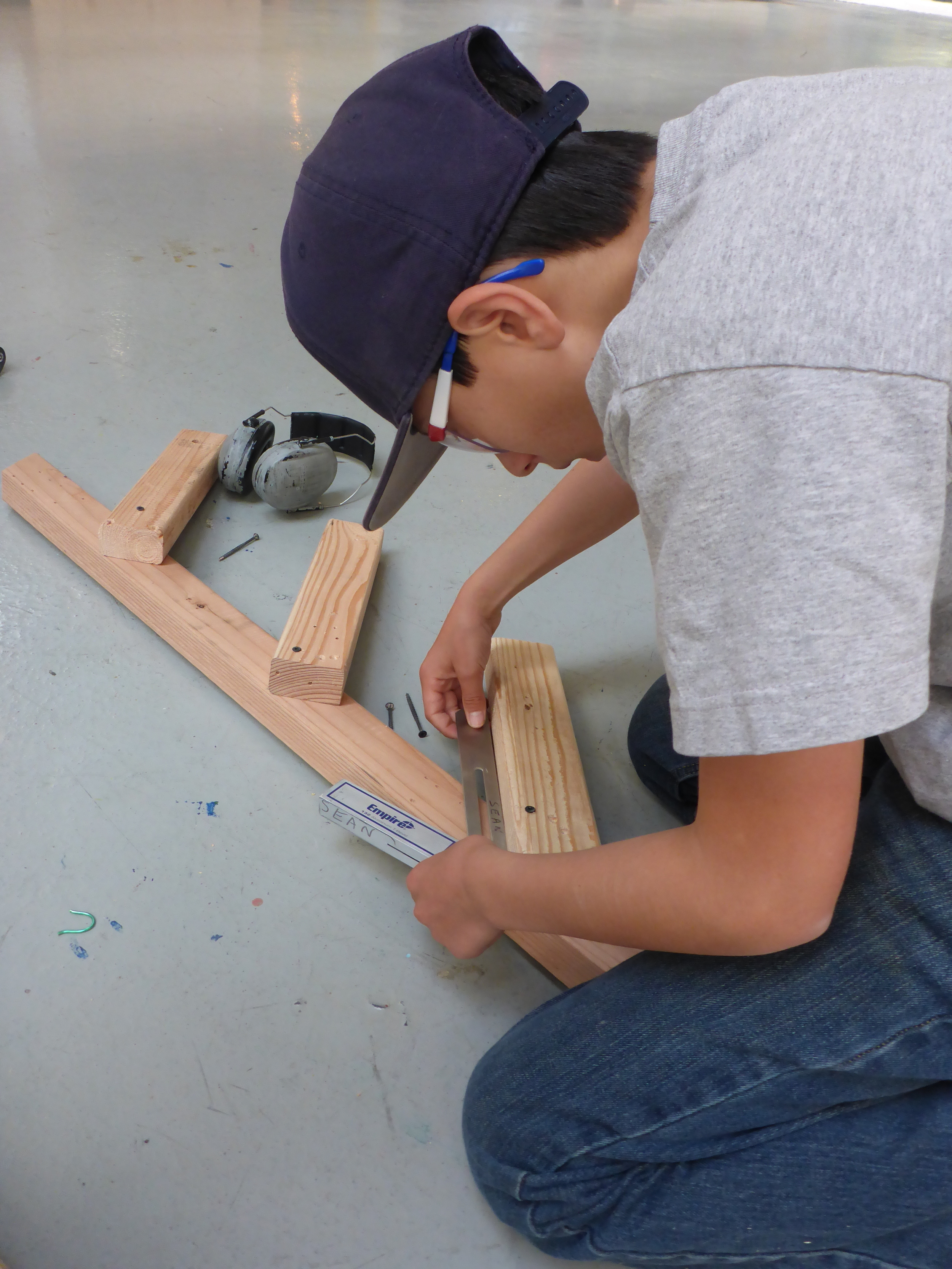 Alex measures the angles of one side of the stairs.