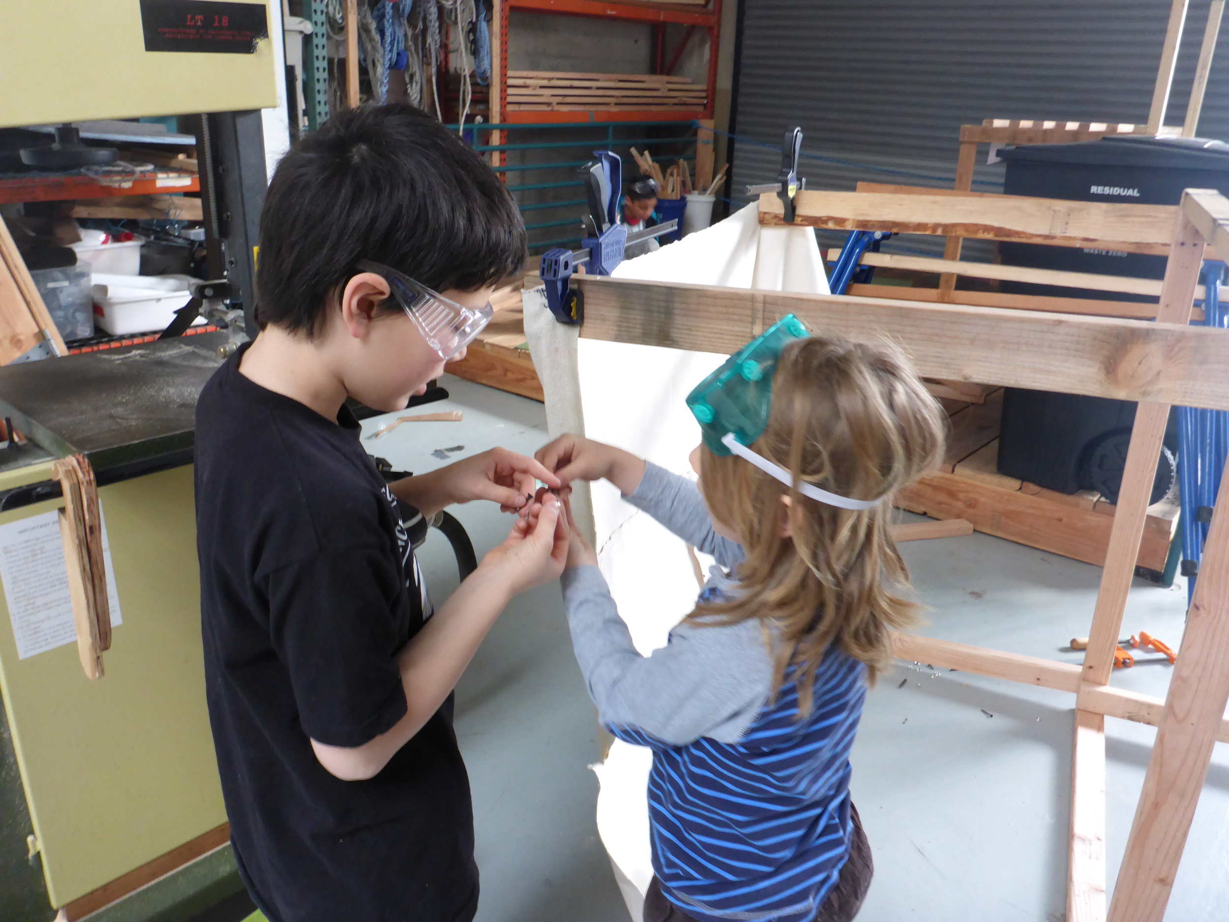 Ayden shows Eli how to put the finish washer and screws together to attach the awning.